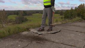 Εργαζόμενος με τη βαρειά που προσπαθεί να ξαναβάλει τις τσιμεντένιες πλάκες απόθεμα βίντεο
