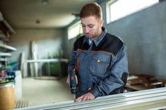 Εργαζόμενος με τη διάτρυση του mashine στο εργαστήριο Στοκ Φωτογραφία