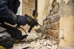 Εργαζόμενος με το ηλεκτρικό σφυρί που καθαρίζει τον τούβλινο τοίχο Στοκ φωτογραφία με δικαίωμα ελεύθερης χρήσης