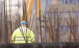 Εργαζόμενος με το μπλε helmeth πίσω από armature στην κατασκευή Στοκ εικόνα με δικαίωμα ελεύθερης χρήσης