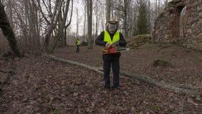 Εργαζόμενος με το πεσμένο δέντρο αλυσιδοπριόνων και τηλεφώνων πλησίον απόθεμα βίντεο