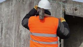 Εργαζόμενος με το σφυρί ελκήθρων ενάντια στον τοίχο φιλμ μικρού μήκους