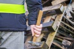 Εργαζόμενος με το σφυρί κοντά στις ξύλινες παλέτες στοκ φωτογραφία με δικαίωμα ελεύθερης χρήσης