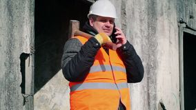 Εργαζόμενος με το τηλέφωνο κυττάρων και σφυρί ελκήθρων κοντά στον τοίχο φιλμ μικρού μήκους