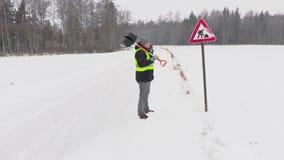 Εργαζόμενος με το φτυάρι χιονιού στη χιονώδη ημέρα κοντά στο οδικό σημάδι απόθεμα βίντεο