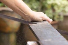 Εργαζόμενος ξυλουργών που πριονίζει τον ξύλινο πίνακα με το πριόνι χεριών στοκ φωτογραφία με δικαίωμα ελεύθερης χρήσης