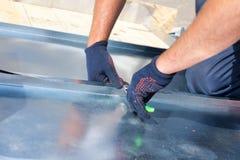 Εργαζόμενος οικοδόμων Roofer που τελειώνει διπλώνοντας ένα φύλλο μετάλλων που χρησιμοποιεί τις ειδικές πένσες με ένα μεγάλο επίπε στοκ φωτογραφία