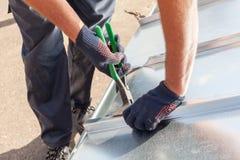 Εργαζόμενος οικοδόμων Roofer που τελειώνει διπλώνοντας ένα φύλλο μετάλλων που χρησιμοποιεί τις ειδικές πένσες με ένα μεγάλο επίπε στοκ εικόνα με δικαίωμα ελεύθερης χρήσης