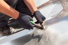 Εργαζόμενος οικοδόμων Roofer που τελειώνει διπλώνοντας ένα φύλλο μετάλλων που χρησιμοποιεί τις ειδικές πένσες με ένα μεγάλο επίπε στοκ φωτογραφία με δικαίωμα ελεύθερης χρήσης