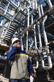 Εργαζόμενος πετρελαίου που μιλά στο τηλέφωνο μέσα στις εγκαταστάσεις καθαρισμού Στοκ Εικόνες