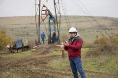 Εργαζόμενος πετρελαίου σε ομοιόμορφο και το κράνος, με το κινητό τηλέφωνο Στοκ φωτογραφίες με δικαίωμα ελεύθερης χρήσης