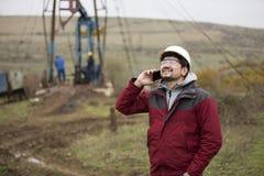 Εργαζόμενος πετρελαίου σε ομοιόμορφο και το κράνος, με το κινητό τηλέφωνο Στοκ Φωτογραφία