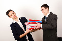 Εργαζόμενος που λαμβάνει πολλά αρχεία από τον ευτυχή προϊστάμενό του. Στοκ Εικόνες