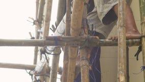 Εργαζόμενος που αναρριχείται στο ικρίωμα μπαμπού με χωρίς παπούτσια απόθεμα βίντεο