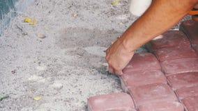 Εργαζόμενος που βάζει την πλάκα επίστρωσης πετρών κίνηση αργή απόθεμα βίντεο