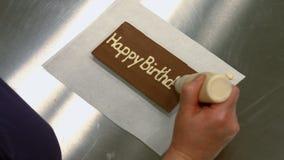 Εργαζόμενος που γράφει χρόνια πολλά σε μια πινακίδα σοκολάτας φιλμ μικρού μήκους