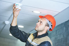 Εργαζόμενος που εγκαθιστά τον ανιχνευτή καπνού στο ανώτατο όριο Στοκ Εικόνα