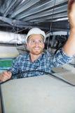 Εργαζόμενος που εγκαθιστά τον ανιχνευτή καπνού στο ανώτατο όριο στοκ φωτογραφία με δικαίωμα ελεύθερης χρήσης