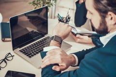Εργαζόμενος που εξετάζει το ρολόι στο γραφείο στην αρχή στοκ εικόνες με δικαίωμα ελεύθερης χρήσης