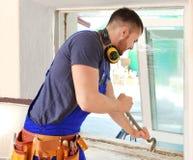 Εργαζόμενος που επισκευάζει το παράθυρο στοκ εικόνα με δικαίωμα ελεύθερης χρήσης