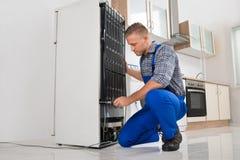 Εργαζόμενος που επισκευάζει το ψυγείο στο εσωτερικό στοκ εικόνες