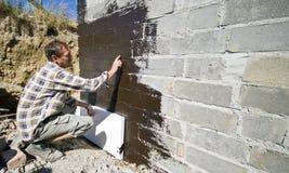 Εργαζόμενος που εφαρμόζει το πολυστυρόλιο στοκ εικόνες