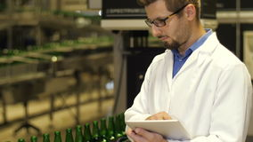 Εργαζόμενος που ελέγχει τα μπουκάλια σε μια γραμμή μεταφορέων απόθεμα βίντεο