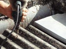 Εργαζόμενος που καθορίζει τη βρώμικη παλαιά στέγη με το ηλεκτρικό κατσαβίδι τρυπανιών Στοκ Φωτογραφίες