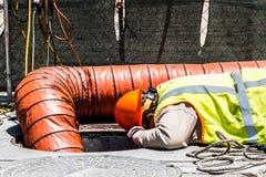 Εργαζόμενος που κοιτάζει κάτω από την καταπακτή στοκ εικόνα