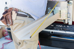 Εργαζόμενος που μετρά την επεξεργασία υδρορροών βροχής μέσω της άνευ ραφής διαμόρφωσης στοκ εικόνες με δικαίωμα ελεύθερης χρήσης