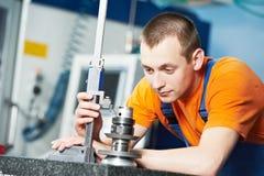 Εργαζόμενος που μετρά το τέμνον εργαλείο στοκ εικόνες
