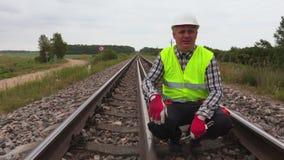 Εργαζόμενος που μιλά και που παρουσιάζει χειρονομίες στη διαδρομή σιδηροδρόμων απόθεμα βίντεο