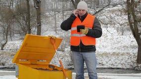 Εργαζόμενος που μιλά στο τηλέφωνο κυττάρων κοντά στο Sandbox το χειμώνα φιλμ μικρού μήκους