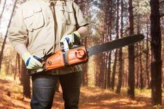 Εργαζόμενος που στέκεται με το αλυσιδοπρίονο στο δάσος Στοκ εικόνα με δικαίωμα ελεύθερης χρήσης