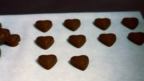 Εργαζόμενος που τακτοποιεί διαμορφωμένη την καρδιά σκοτεινή σοκολάτα στο δίσκο απόθεμα βίντεο