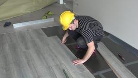 Εργαζόμενος που τοποθετεί κάτω από τους φυλλόμορφους ξύλινους πίνακες δαπέδων μαζί με τη μεγάλη προσοχή απόθεμα βίντεο
