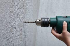 Εργαζόμενος που τρυπά μια τρύπα με τρυπάνι στον τοίχο με ένα ηλεκτρικό τρυπάνι Στοκ Εικόνες