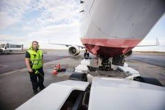 Εργαζόμενος που υπερασπίζεται το αεροπλάνο με το καλώδιο επικοινωνίας στο διάδρομο στοκ εικόνες
