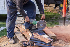 Εργαζόμενος που χρησιμοποιεί ένα κυκλικό πριόνι χεριών για να κόψει το στέγη-κεραμίδι Στοκ Εικόνες