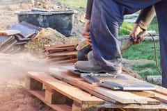 Εργαζόμενος που χρησιμοποιεί ένα κυκλικό πριόνι χεριών για να κόψει το στέγη-κεραμίδι Στοκ εικόνα με δικαίωμα ελεύθερης χρήσης