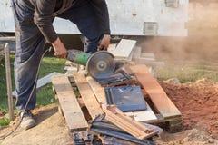Εργαζόμενος που χρησιμοποιεί ένα κυκλικό πριόνι χεριών για να κόψει ένα στέγη-κεραμίδι Στοκ Εικόνες