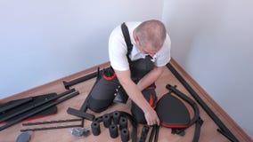Εργαζόμενος που χρησιμοποιεί την ταμπλέτα κοντά στα τμήματα μηχανών άσκησης απόθεμα βίντεο
