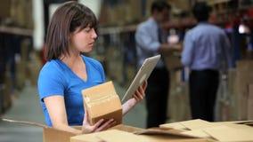 Εργαζόμενος που χρησιμοποιεί την ψηφιακή ταμπλέτα για να ελέγξει τα κιβώτια απόθεμα βίντεο