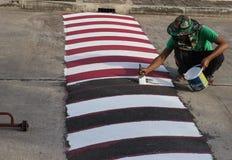 Εργαζόμενος που χρησιμοποιεί τη βούρτσα για τη ζωγραφική της άσπρης γραμμής στο δρόμο Στοκ Εικόνες