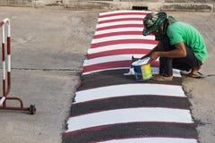 Εργαζόμενος που χρησιμοποιεί τη βούρτσα για τη ζωγραφική της άσπρης γραμμής στο δρόμο Στοκ εικόνα με δικαίωμα ελεύθερης χρήσης