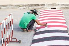 Εργαζόμενος που χρησιμοποιεί τη βούρτσα για τη ζωγραφική της άσπρης γραμμής στο δρόμο Στοκ Εικόνα