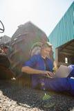 Εργαζόμενος που χρησιμοποιεί το lap-top στο δρόμο μια ηλιόλουστη ημέρα Στοκ Εικόνες