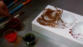 Εργαζόμενος που χρωματίζει μια φόρμα σοκολάτας που χρησιμοποιεί τη χρωματισμένη σοκολάτα φιλμ μικρού μήκους
