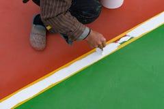 Εργαζόμενος που χρωματίζει το περιθώριο στο πάτωμα για το υπαίθριο στάδιο Στοκ Φωτογραφία