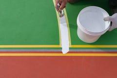 Εργαζόμενος που χρωματίζει το περιθώριο στο πάτωμα για το υπαίθριο στάδιο Στοκ Εικόνα